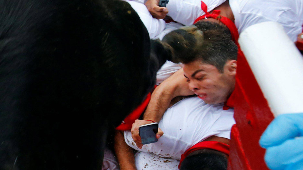 A wild cow hits a reveller with its hoof as it enters the bullring following the seventh running of the bulls at the San Fermin festival in Pamplona, northern Spain, July 13, 2017. REUTERS/Susana VeraCODE: X01622