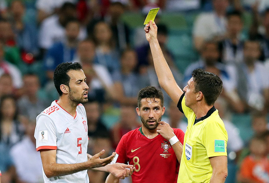 Sochi (Russian Federation), 15/06/2018.- Referee Gianluca Rocchi shows Sergio Busquets (L) of Spain the yellow card during the FIFA World Cup 2018 group B preliminary round soccer match between Portugal and Spain in Sochi, Russia, 15 June 2018. (RESTRICTIONS APPLY: Editorial Use Only, not used in association with any commercial entity - Images must not be used in any form of alert service or push service of any kind including via mobile alert services, downloads to mobile devices or MMS messaging - Images must appear as still images and must not emulate match action video footage - No alteration is made to, and no text or image is superimposed over, any published image which: (a) intentionally obscures or removes a sponsor identification image; or (b) adds or overlays the commercial identification of any third party which is not officially associated with the FIFA World Cup) (España, Mundial de Fútbol, Rusia) EFE/EPA/FRIEDEMANN VOGEL EDITORIAL USE ONLY