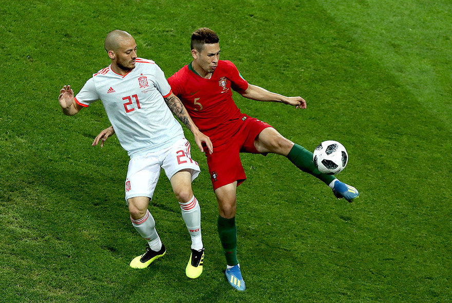 Sochi (Russian Federation), 15/06/2018.- David Silva of Spain (L) and Raphael Guerreiro of Portugal in action during the FIFA World Cup 2018 group B preliminary round soccer match between Portugal and Spain in Sochi, Russia, 15 June 2018. (RESTRICTIONS APPLY: Editorial Use Only, not used in association with any commercial entity - Images must not be used in any form of alert service or push service of any kind including via mobile alert services, downloads to mobile devices or MMS messaging - Images must appear as still images and must not emulate match action video footage - No alteration is made to, and no text or image is superimposed over, any published image which: (a) intentionally obscures or removes a sponsor identification image; or (b) adds or overlays the commercial identification of any third party which is not officially associated with the FIFA World Cup) (España, Mundial de Fútbol, Rusia) EFE/EPA/MOHAMED MESSARA EDITORIAL USE ONLY EDITORIAL USE ONLY