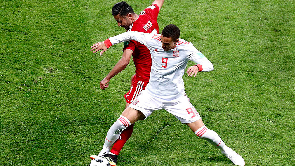 Kazan (Russian Federation), 20/06/2018.- Omid Ebrahimi (L) of Iran and Rodrigo of Spain in action during the FIFA World Cup 2018 group B preliminary round soccer match between Iran and Spain in Kazan, Russia, 20 June 2018. (RESTRICTIONS APPLY: Editorial Use Only, not used in association with any commercial entity - Images must not be used in any form of alert service or push service of any kind including via mobile alert services, downloads to mobile devices or MMS messaging - Images must appear as still images and must not emulate match action video footage - No alteration is made to, and no text or image is superimposed over, any published image which: (a) intentionally obscures or removes a sponsor identification image; or (b) adds or overlays the commercial identification of any third party which is not officially associated with the FIFA World Cup) (España, Mundial de Fútbol, Rusia) EFE/EPA/SERGEY DOLZHENKO EDITORIAL USE ONLY EDITORIAL USE ONLY