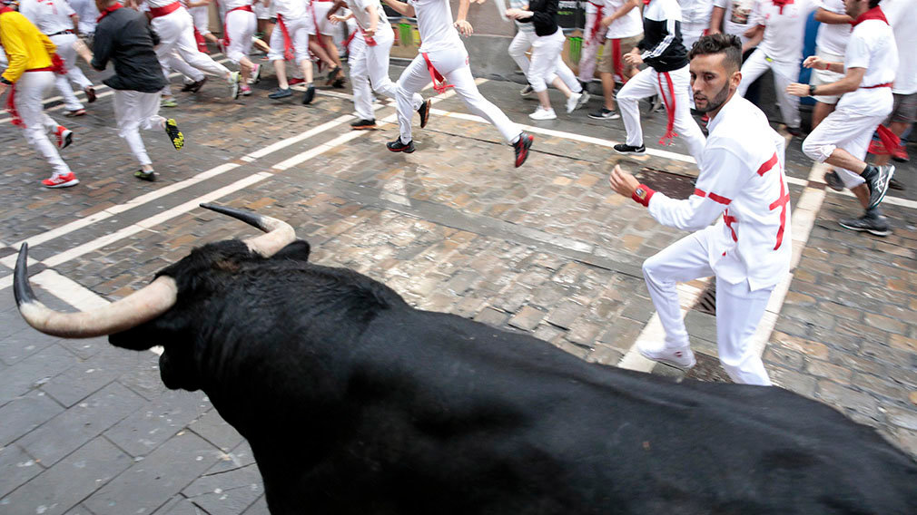 070718-4. Pamplona (Spain), 07/07/2018.- A fighting bull from the ranch of Puerto de San Lorenzo stampedes around a corner in the first 'encierro' or running-with-the-bulls during the Festival of San Fermin 2018 in Pamplona, Spain, 07 July 2018. The festival, locally known as Sanfermines, is held annually from 06 to 14 July in commemoration of the city's patron saint. Hundreds of thousands of visitors from all over the world attend the fiesta. Many of them physically participate in the highlight event - the running of the bulls, or encierro - where they attempt to outrun the bulls along a route through the narrow streets of the old city. (España, Estados Unidos) EFE/EPA/JIM HOLLANDER