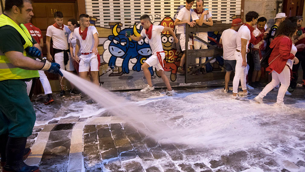 PAM01. Pamplona (Spain), 08/07/2018.- A reveller runs pas placards of bull cartoons as he tries to avoid a city worker spraying water to clean the fifth of the streets after a heavy night partying during the Festival of San Fermin 2018 in Pamplona, Spain, 08 July 2018. The festival, locally known as Sanfermines, is held annually from 06 to 14 July in commemoration of the city's patron saint. Hundreds of thousands of visitors from all over the world attend the fiesta. Many of them physically participate in the highlight event - the running of the bulls, or encierro - where they attempt to outrun the bulls along a route through the narrow streets of the old city. (España, Estados Unidos) EFE/EPA/JIM HOLLANDER