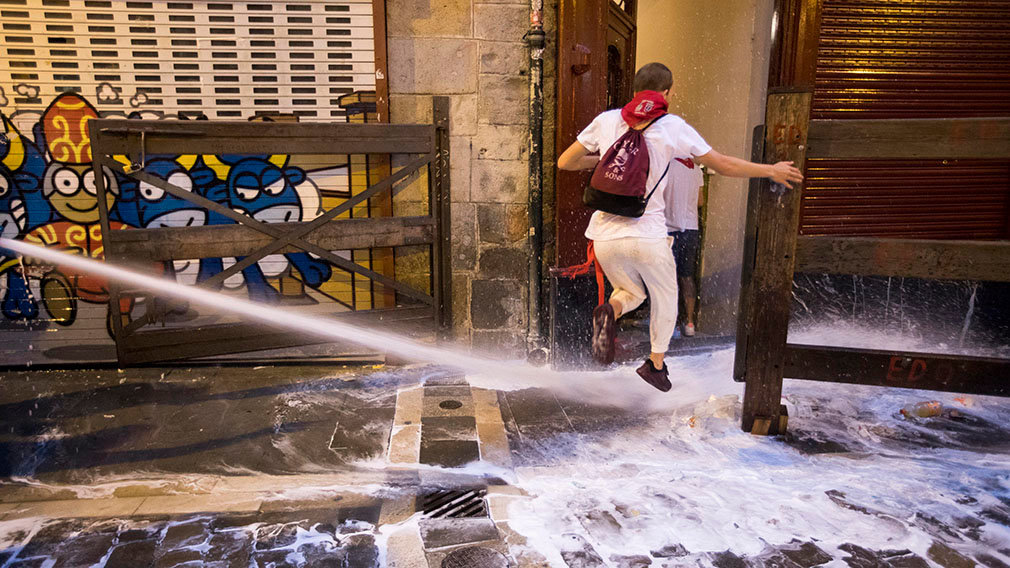 PAM01. Pamplona (Spain), 08/07/2018.- A reveller jumps over water that is sprayed by a city worker to clean the fifth of the streets after a heavy night partying during the Festival of San Fermin 2018 in Pamplona, Spain, 08 July 2018. The festival, locally known as Sanfermines, is held annually from 06 to 14 July in commemoration of the city's patron saint. Hundreds of thousands of visitors from all over the world attend the fiesta. Many of them physically participate in the highlight event - the running of the bulls, or encierro - where they attempt to outrun the bulls along a route through the narrow streets of the old city. (España, Estados Unidos) EFE/EPA/JIM HOLLANDER