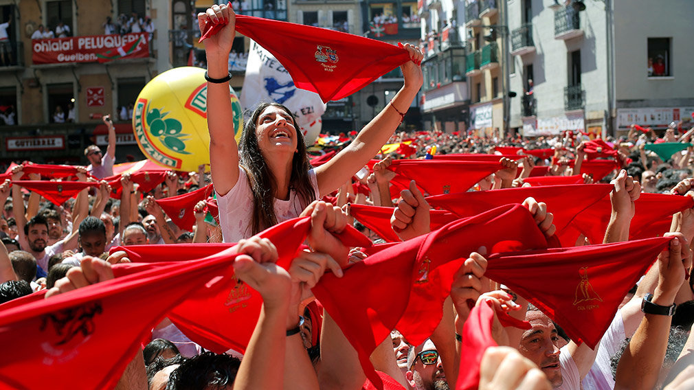 Revellers hold up traditional red scarves before the firing of 'chupinazo', which opens the San Fermin festival in Pamplona Spain, July 6, 2019.  *** Local Caption *** .