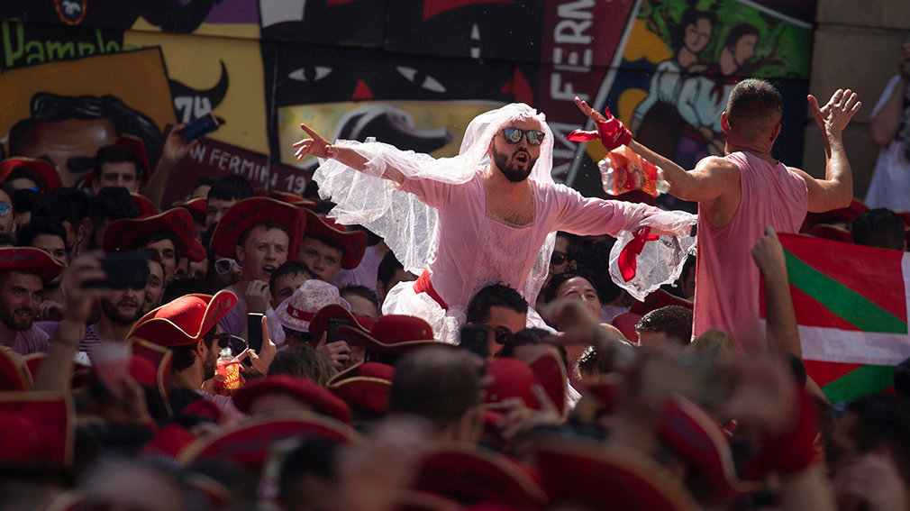 PAM04. Pamplona (Spain), 06/07/2019.- A man in a bridal dress sits on shoulders in the crowd during heavy drinking as the Fiesta de San Fermin kicks off in Pamplona, northern Spain, 06 July 2019. The famed fiesta is renowned for its morning running-with-the bulls each day for eight days and it non-stop partying atmosphere, al made internationally famous by American novelist Ernest Hemingway in his 1926 novel The Sun Also Rises. (España) EFE/EPA/JIM HOLLANDER