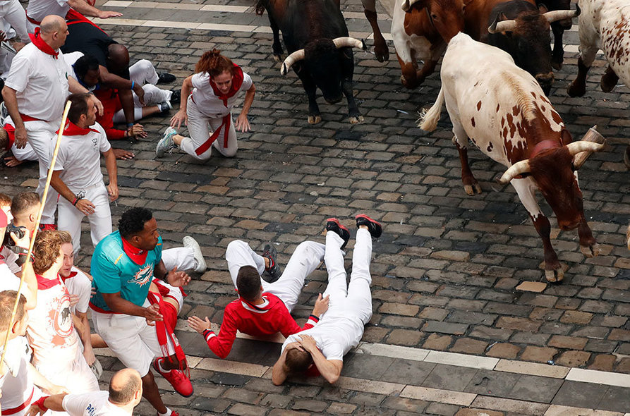 Revellers sprint near bulls and steers during the second running of the bulls at the San Fermin festival in Pamplona, Spain, July 8, 2019.