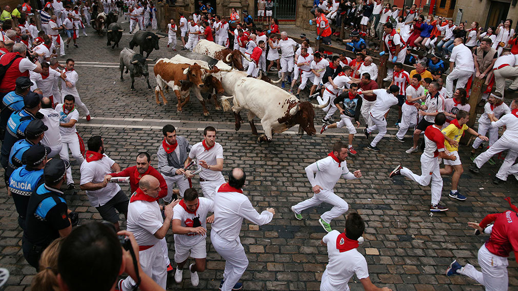 Revellers sprint near bulls and steers during the running of the bulls at the San Fermin festival in Pamplona, Spain, July 9, 2019.   *** Local Caption *** .