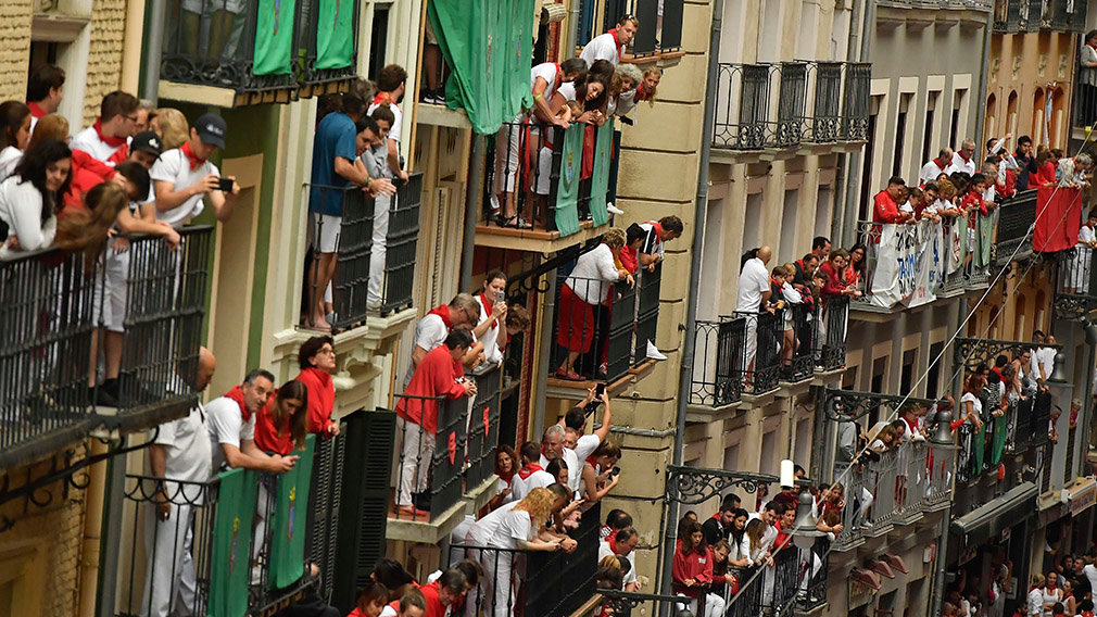 People on balconies wait for the start of the running of the bulls at the San Fermin Festival in Pamplona, northern Spain, Tuesday, July 9, 2019