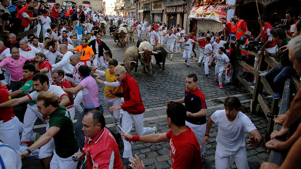 Revellers sprint near bulls and steers during the running of the bulls at the San Fermin festival in Pamplona, Spain, July 12, 2019.