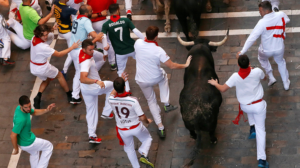 Revellers sprint near bulls and steers during the running of the bulls at the San Fermin festival in Pamplona, Spain, July 12, 2019. REUTERS/Susana Vera