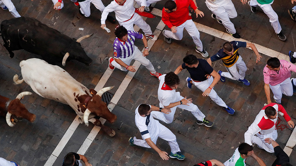 Revellers sprint near bulls and steers during the running of the bulls at the San Fermin festival in Pamplona, Spain, July 12, 2019.  *** Local Caption *** .