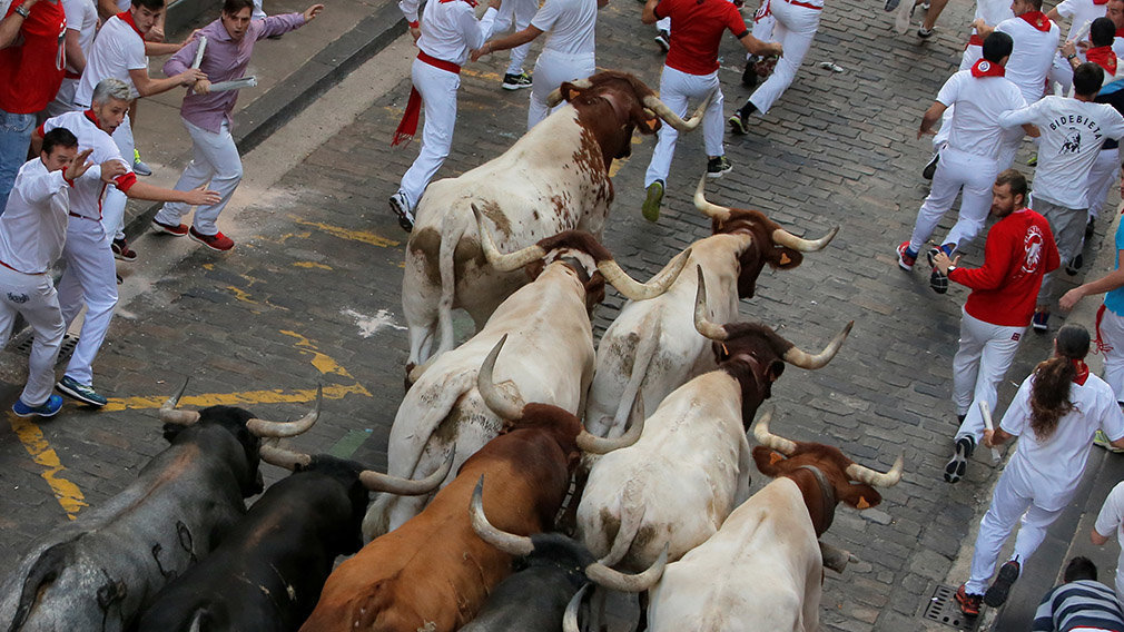 Runners participate in the running of the bulls, during the San Fermin festival in Pamplona, Spain July 14, 2019.   *** Local Caption *** .