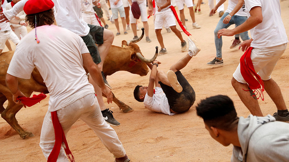 A wild cow hits a reveller inside the bullring after the running of the bulls at the San Fermin festival in Pamplona, Spain, July 14, 2019.   *** Local Caption *** .