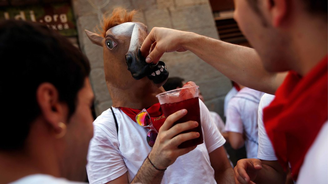 A reveller attempts to drink without removing his horse mask during the start of the San Fermin festival in Pamplona, northern Spain, July 6, 2016. REUTERS/Susana Vera