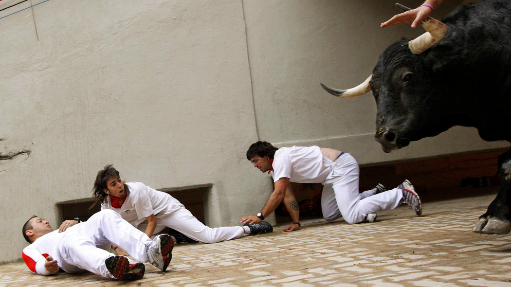 Sergio Colas (C) moves away from the path of an El Pilar fighting bull after falling at the entrance to the bullring during the seventh running of the bulls at the San Fermin festival in Pamplona, northern Spain, July 13, 2011. This year Sergio Colas celebrates his 20th year of running with the bulls in Pamplona, where he started as a 15 year old kid following in the footsteps of his father.