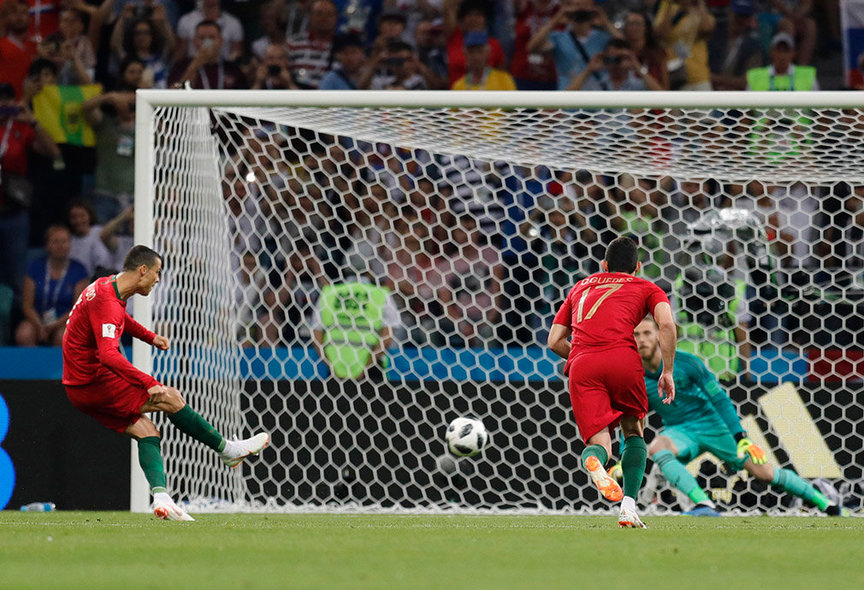 Sochi (Russian Federation), 15/06/2018.- Cristiano Ronaldo (L) of Portugal score the 1-0 goal from the penalty spot during the FIFA World Cup 2018 group B preliminary round soccer match between Portugal and Spain in Sochi, Russia, 15 June 2018. (RESTRICTIONS APPLY: Editorial Use Only, not used in association with any commercial entity - Images must not be used in any form of alert service or push service of any kind including via mobile alert services, downloads to mobile devices or MMS messaging - Images must appear as still images and must not emulate match action video footage - No alteration is made to, and no text or image is superimposed over, any published image which: (a) intentionally obscures or removes a sponsor identification image; or (b) adds or overlays the commercial identification of any third party which is not officially associated with the FIFA World Cup) (España, Mundial de Fútbol, Rusia) EFE/EPA/RONALD WITTEK EDITORIAL USE ONLY