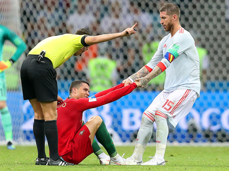 Sochi (Russian Federation), 15/06/2018.- Cristiano Ronaldo (C) of Portugal and Sergio Ramos (R) of Spain react during the FIFA World Cup 2018 group B preliminary round soccer match between Portugal and Spain in Sochi, Russia, 15 June 2018. At left Italian referee Gianlucca Rocchi. The match ended 3-3. (RESTRICTIONS APPLY: Editorial Use Only, not used in association with any commercial entity - Images must not be used in any form of alert service or push service of any kind including via mobile alert services, downloads to mobile devices or MMS messaging - Images must appear as still images and must not emulate match action video footage - No alteration is made to, and no text or image is superimposed over, any published image which: (a) intentionally obscures or removes a sponsor identification image; or (b) adds or overlays the commercial identification of any third party which is not officially associated with the FIFA World Cup) (España, Mundial de Fútbol, Rusia) EFE/EPA/FRIEDEMANN VOGEL EDITORIAL USE ONLY