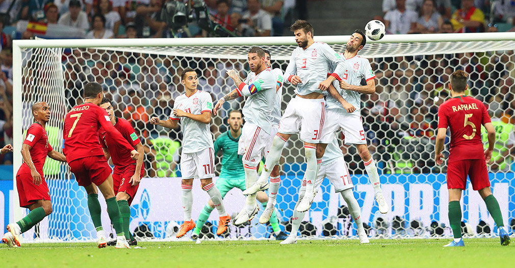 Sochi (Russian Federation), 15/06/2018.- Cristiano Ronaldo (2-L) of Portugal converts a free kick to score the 3-3 equalizer during the FIFA World Cup 2018 group B preliminary round soccer match between Portugal and Spain in Sochi, Russia, 15 June 2018. (RESTRICTIONS APPLY: Editorial Use Only, not used in association with any commercial entity - Images must not be used in any form of alert service or push service of any kind including via mobile alert services, downloads to mobile devices or MMS messaging - Images must appear as still images and must not emulate match action video footage - No alteration is made to, and no text or image is superimposed over, any published image which: (a) intentionally obscures or removes a sponsor identification image; or (b) adds or overlays the commercial identification of any third party which is not officially associated with the FIFA World Cup) (España, Mundial de Fútbol, Rusia) EFE/EPA/FRIEDEMANN VOGEL EDITORIAL USE ONLY