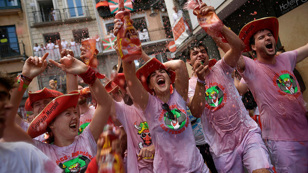 Revellers start celebrating early while waiting for the launch of the 'Chupinazo' rocket, to celebrate the official opening of the 2018 San Fermin fiestas with daily bull runs, bullfights, music and dancing in Pamplona, Spain, Friday July 6, 2018. (