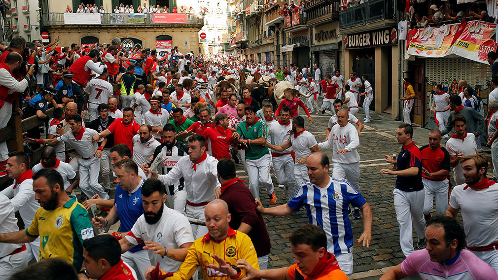 Revellers run next to fighting bulls from Cebada Gago ranch, during the running of the bulls at the San Fermin Festival, in Pamplona, northern Spain, Monday, July 8, 2019.