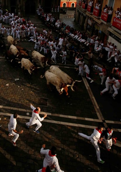 Revellers sprint near bulls and steers during the second running of the bulls at the San Fermin festival in Pamplona, Spain, July 8, 2019. REUTERS/Susana Vera - RC189E3815F0