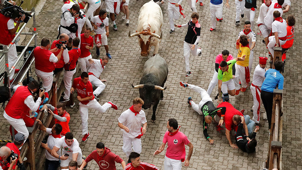 A reveller sprints in front of a bull during the running of the bulls at the San Fermin festival in Pamplona, Spain, July 9, 2019.  *** Local Caption *** .