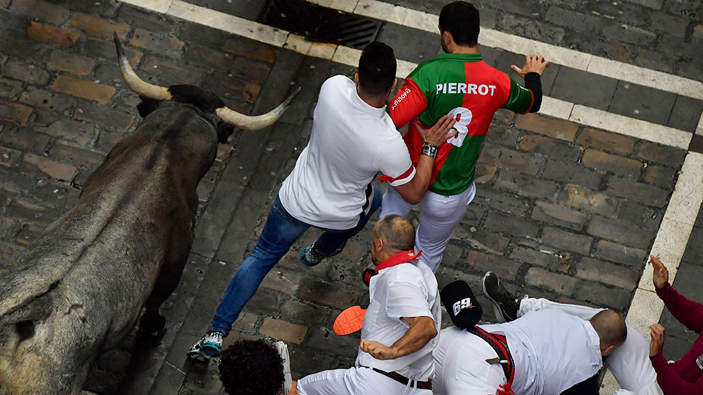 Revellers run next to fighting bulls during the running of the bulls at the San Fermin Festival, in Pamplona, northern Spain, Tuesday, July 9, 2019
