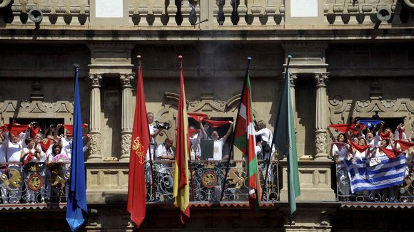 A rocket signalling the beginning of the San Fermin festival is fired between the Basque and Spanish flags at the town hall in Pamplona, Spain July 6, 2015. The San Fermin festival, best known for its daily running of the bulls, kicked off on Monday