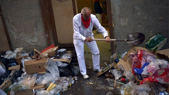 "A man clears rubbish from his doorway on the seventh day of the San Fermin festival in Pamplona, northern Spain, July 12, 2015. The festival, a heady mix of drinking, dancing, late nights and bullfights, made famous by Ernest Hemingway in his novel ""The Sun Also Rises"", runs for nine days until July 14. REUTERS/Vincent West"