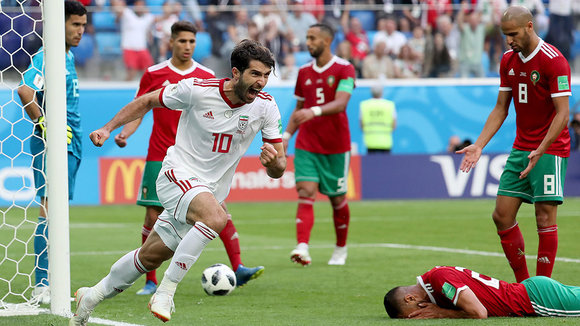 St.petersburg (Russian Federation), 15/06/2018.- Karim Ansarifard of Iran (front) celebrates after Aziz Bouhaddouz of Morocco (down) scored an own goal during the FIFA World Cup 2018 group B preliminary round soccer match between Morocco and Iran in St.Petersburg, Russia, 15 June 2018.