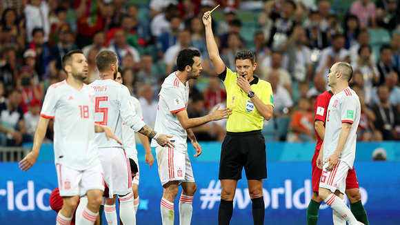 Sochi (Russian Federation), 15/06/2018.- Referee Gianluca Rocchi shows Sergio Busquets (center L) of Spain the yellow card during the FIFA World Cup 2018 group B preliminary round soccer match between Portugal and Spain in Sochi, Russia, 15 June 2018.