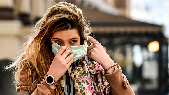 24 February 2020, Italy, Milan: A pedestrian puts on a surgical mask on her face amid the outbreak of the coronavirus. Photo: Claudio Furlan/LaPresse via ZUMA Press/dpa ONLY FOR USE IN SPAIN  24 February 2020, Italy, Milan: A pedestrian puts on a surgical mask on her face amid the outbreak of the coronavirus. Photo: Claudio Furlan/LaPresse via ZUMA Press/dpa  2/24/2020 ONLY FOR USE IN SPAIN