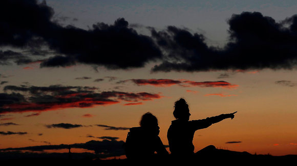 People are silhouetted against a orange colored sky at sunset in Ripagaina, near Pamplona, Spain, 10 November 2020. EFE/ Jesús Diges