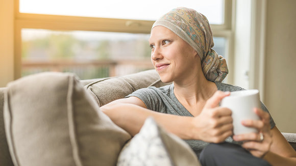 Ethnic young adult female cancer patient sipping tea while at home