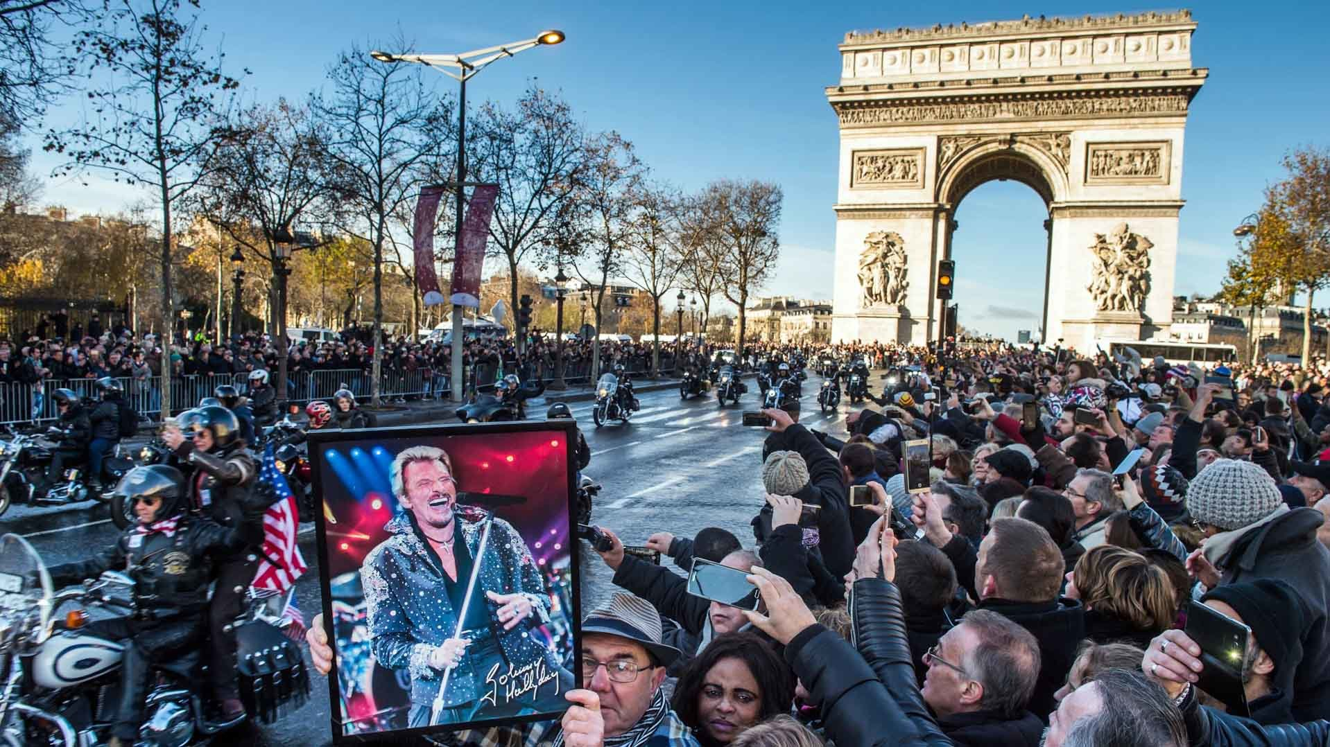 Paris (France), 09/12/2017.- A fan holds a poster of French singer Johnny Hallyday during his funeral procession at the Champs Elysees in Paris, France, 09 December 2017. Johnny Hallyday, France's biggest rock star, has died of cancer on 06 December. He was 74. (Francia) EFE/EPA/CHRISTOPHE PETIT TESSON