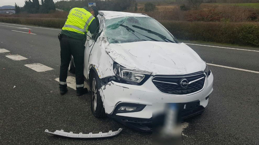 Un agente de la Guardia Civil, junto al coche accidentado en Villanueva de Araquil. GUARDIA CIVIL