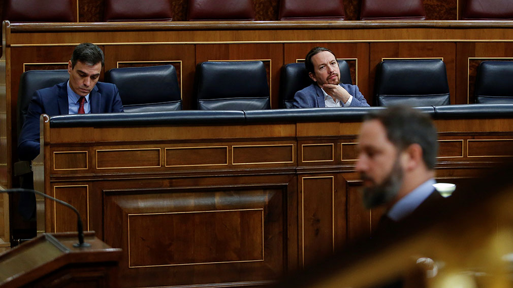 Spanish Prime Minister, Pedro Sanchez (L), chats with Second Deputy Prime Minister, Pablo Iglesias (R), look at far-right Vox party's leader Santiago Abascal (R) as he is in his way to deliver a speech during the plenary session at Lower Chamber of Spanish Parliament, in Madrid, Spain, 09 April 2020. The session is to be focused in passing a new extension of the state of alarm due to coronavirus outbreak. EFE/Mariscal POOL